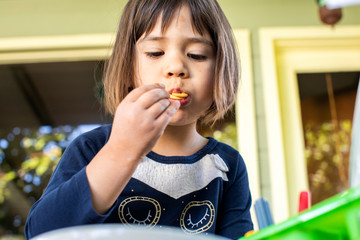 A preschool aged girl eating a cracker outside on a porch.
