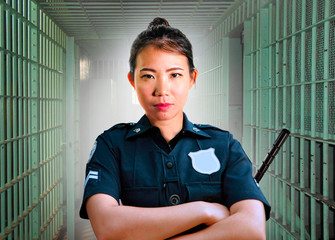 young serious and attractive Asian Korean guard woman standing on cell at State penitentiary wearing police uniform in crime prison punishment and law enforcement