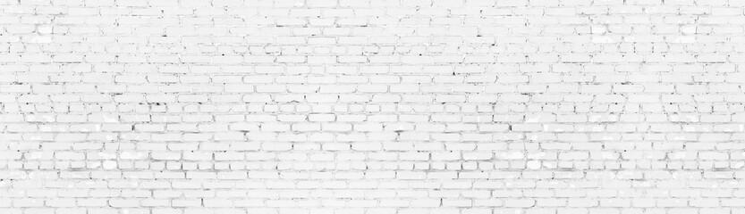 Whitewashed shabby brick wall wide panoramic texture. White painted old brickwork panorama. Long light background