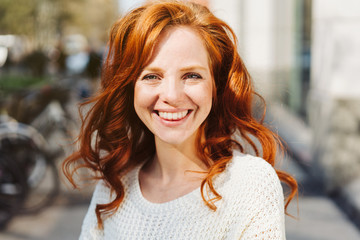 Friendly young redhead woman with vivacious smile