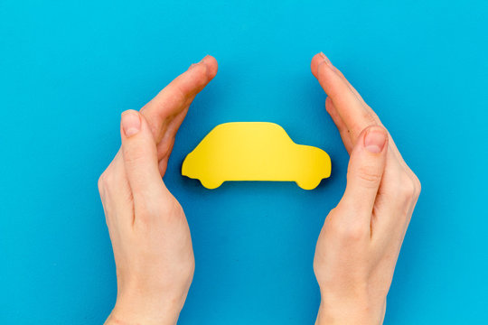 Car insurance concept with car in hands on blue background top view mockup