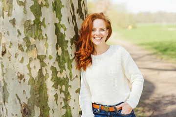 Relaxed happy young woman leaning against a tree