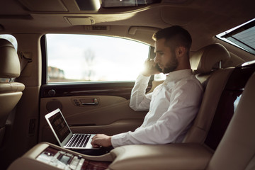 Man uses laptop and talking on smartphone sitting in back seat of car, businessman in taxi
