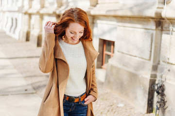 Cheerful young redhead woman walking through town