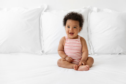 Happy black baby sitting on bed