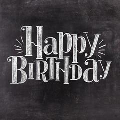 Hand lettering Happy Birthday on retro black chalkboard background. Vintage greeting card design.
