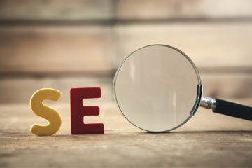 Colorful word Seo with magnifying glass. Search engine optimisation concept