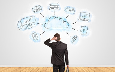 Fototapeta Young businessman in doubt looking to a wall with cloud technology concept  obraz