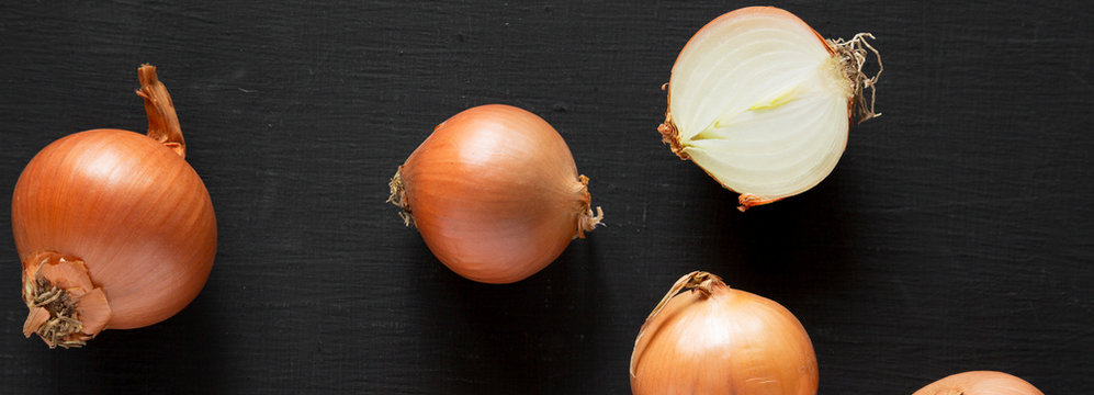 Unpeeled raw yellow onions on a black surface, top view. Flat lay, overhead, from above. Close-up.