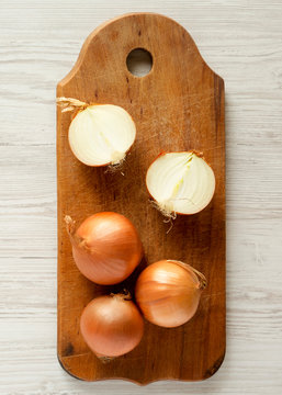 Unpeeled raw organic yellow onions on rustic wooden board over white wooden background, top view. Flat lay, overhead, from above. Close-up.