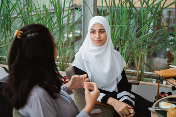 muslim woman talking in cafe together. girl with scarf having a chat