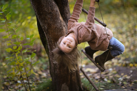 girl child in tree sways on rope ladder