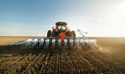 Farmer with tractor seeding soy crops at agricultural field