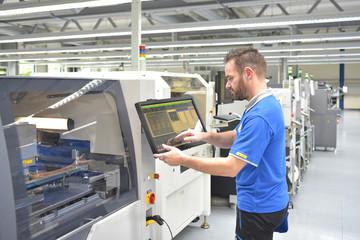 Arbeiter in der Mikroelektronik bedient moderne Maschine zur Fertigung von Bauteilen -...