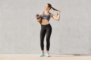 Full length photo of healthy young woman in sportswear holding yoga mat, touches her ponytail, be photographed after training, model posing solated over gray background. Copy space for advertisment.