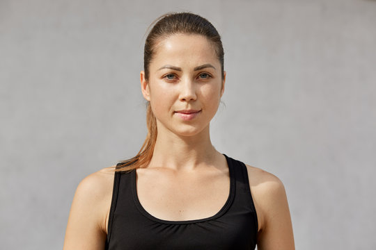 Portrait of confident sporty woman with ponytail standing over gray background and looking at camera, has serious facial expression, wearing black sportwear, ready for working out. Health care concept