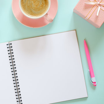 Cup of coffee, gift box and notebook with pen on blue background.