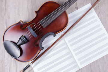 Classical violin with empty music sheet book. Studio shot of old violin. Classical musical instrument