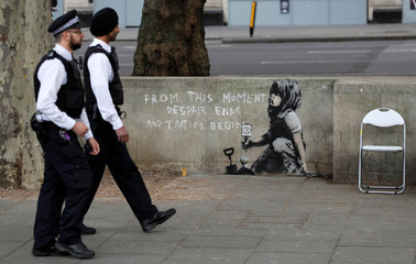 Police officers walk past a graffiti believed to have been created by street artist Banksy, at the site where hundreds of Extinction Rebellion climate protestors camped recently, at Marble Arch in London