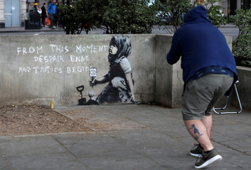 A passer-by photographs a graffiti believed to have been created by street artist Banksy, at the site where hundreds of Extinction Rebellion climate protestors camped recently, at Marble Arch in London