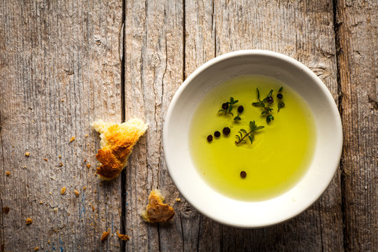 olive oil on a small plate with herbs and peppercorns