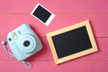 Beauty blogger accessories. Modern polaroid photo camera, picture frame and image on pink wooden background. Top view, flat lay composition, overhead.