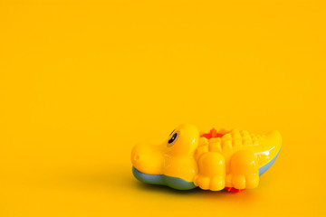 Crocodile toy isolated on a yellow background.