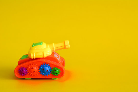 Toy tank isolated on a yellow background.