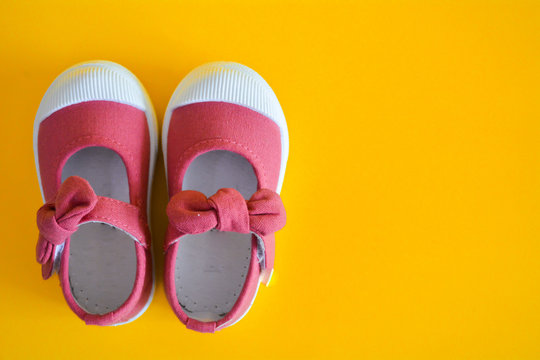 Pink shoes for children isolated on a yellow background.