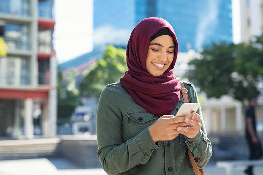 Islamic woman in hijab using phone