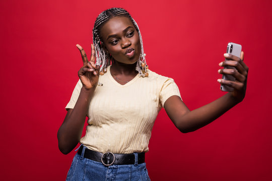 Young African American woman taking a selfie isolated on red background