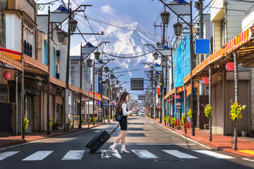Wall Mural - Woman walking on the road in Fujiyoshida with background of Fuji mountain, Japan.