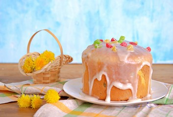 Traditional Easter cake on a white plate, decorated with icing sugar and candied fruits. Happy Easter.
