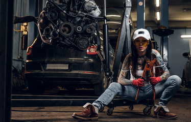 Stylish tattooed girl holding a big wrench while sitting on a hydraulic hoist with a suspended car engine in the workshop
