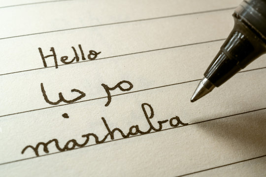 Beginner Arabic language learner writing Hello word Marhaba in abjad Arabic alphabet on a notebook