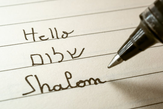 Beginner Hebrew language learner writing Hello Shalom word in Hebrew alphabet on a notebook