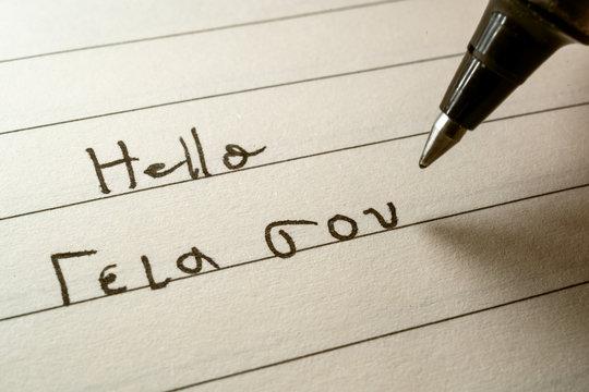 Beginner Greek language learner writing Hello word in greek alphabet on a notebook