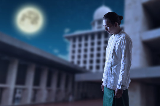 Young Muslim praying in the night, with moon and mosque as background