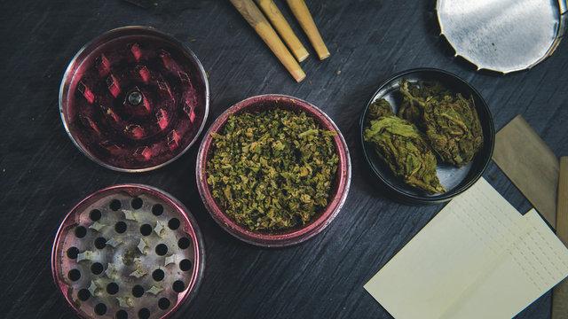 Marijuana buds, joints, paper and lighter lie on dark grey background.