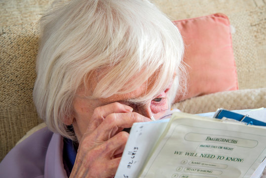 Visually impaired elderly woman with magnifyer