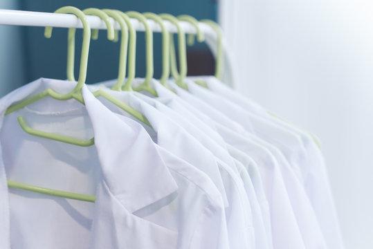 scrubs on hangers. Clean white coats for doctors. medical uniform