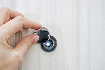 The hand opens the door peephole cover in the front door of light oak. Wall mural