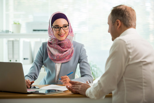 Coworkers meeting in office. Stylish woman in hijab making conversation at desk with man in white modern office. Muslim businesswoman in eyeglasses interviewing man.