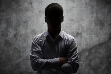 Anonymous man in a business shirt with arms crossed against a dark background