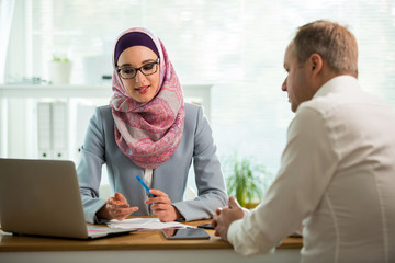 Coworkers meeting in office. Stylish woman in hijab making conversation at desk with man in white...