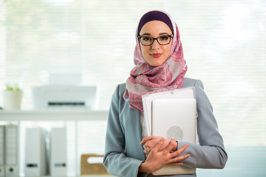 Beautiful young working woman in hijab and eyeglasses smiling in office, holding folders and laptop in arms. Portrait of confident muslim businesswoman. Modern office with big window on background.