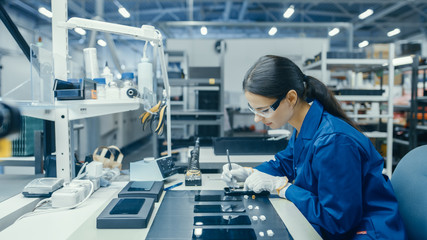 Young Female in Blue Work Coat is Assembling Printed Circuit Boards for Smartphones. Electronics Factory Workers in a High Tech Factory Facility. Wall mural