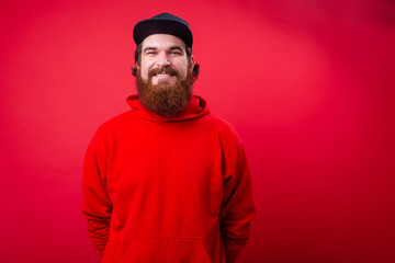 Portrait of handsome bearded guy in red hoody and black hat over isolated wall background Wall mural