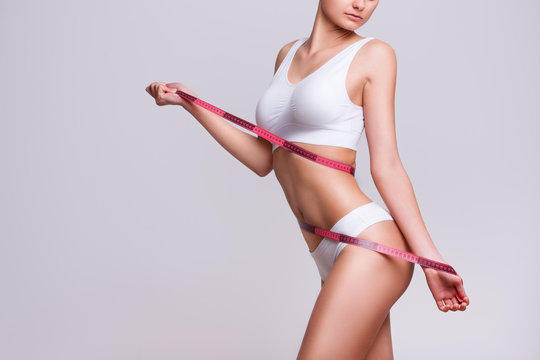 Beauty body care. Woman holding the meter with hands and measuring waist.