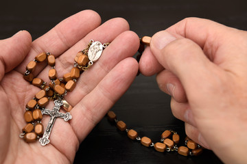 Hands of old man holding a holy rosary from Medjugorje and meditating and praying on the wood beads with crucifix